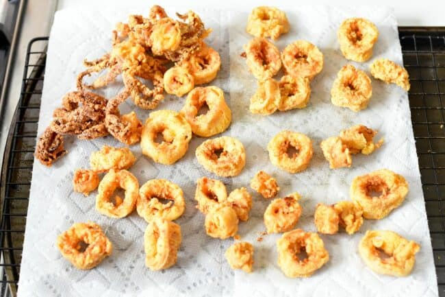 Fried calamari pieces are placed on a sheet of paper towels.