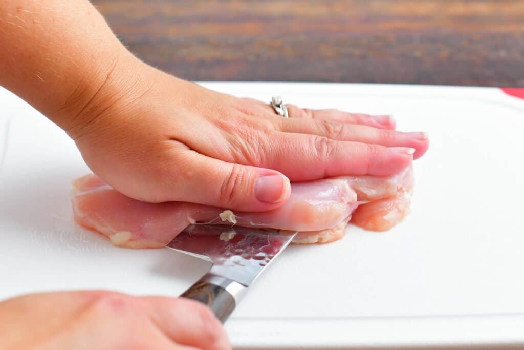 A hand is pressing raw chicken down while a knife is slicing through the middle of the breast.