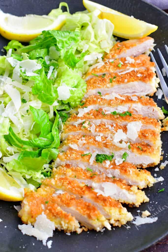 Sliced chicken milanese is placed next to a fresh green side salad.