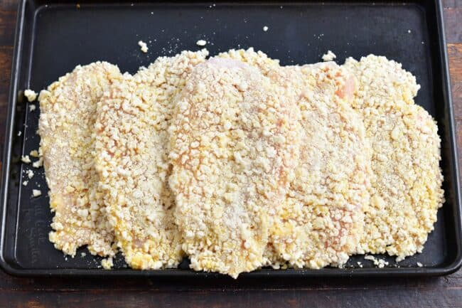 Several panko coated chicken breasts are on a black surface.