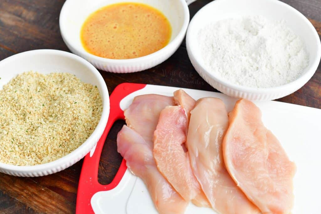 sliced chicken and breading ingredients for chicken parmesan