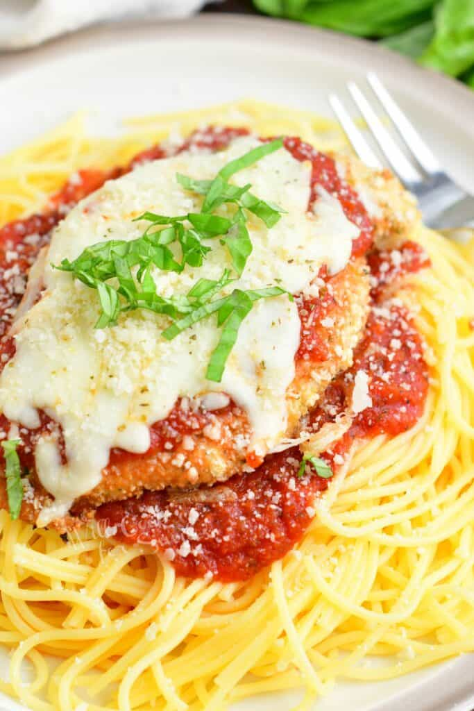 spaghetti topped of with marinara sauce and chicken parmesan