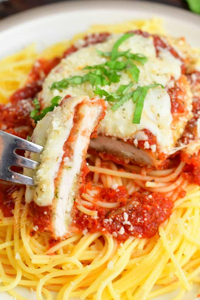chicken parmesan on top of spaghetti with a sliced cut off
