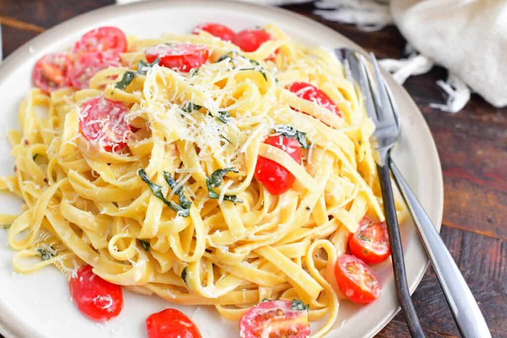 fettuccine in cream sauce with tomatoes and basil on a place with fork and spoon