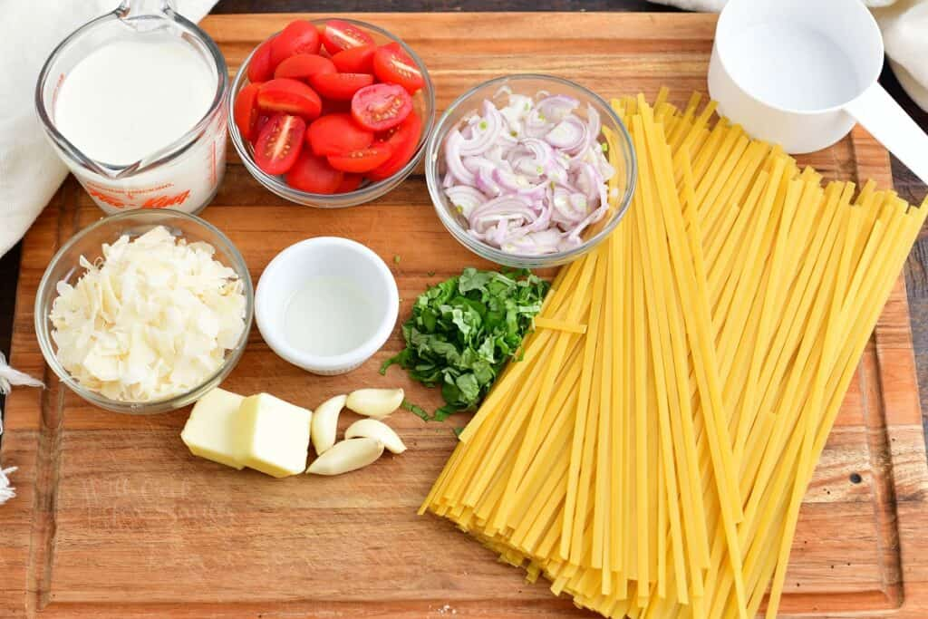ingredients to creamy fettuccine with tomatoes and basil on a cutting board
