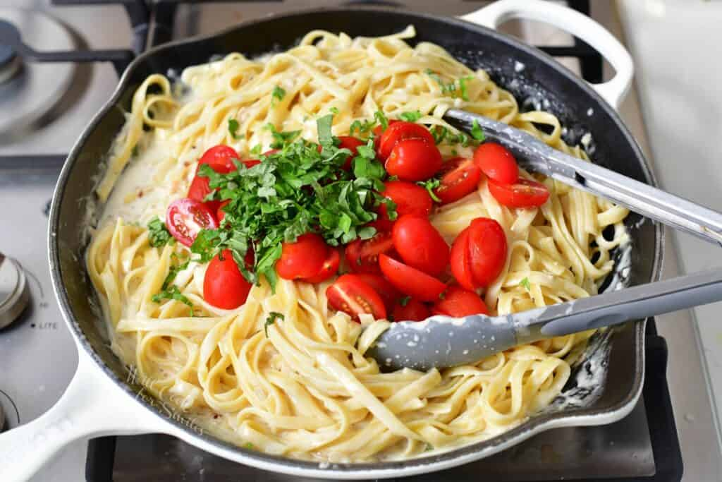 added tomatoes and basil to the pasta in cream sauce in a pan