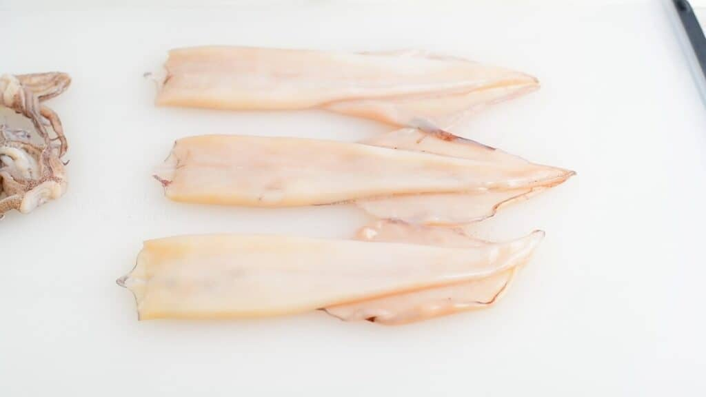 three squid mantle cleaned out with fins attached