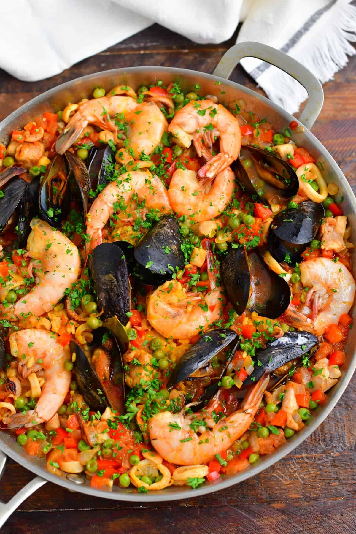 A large pan is filled to the brim with freshly cooked paella.