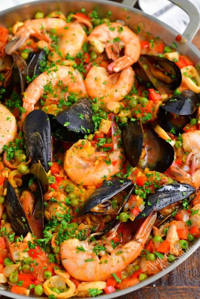 A metal pot is filled with paella.