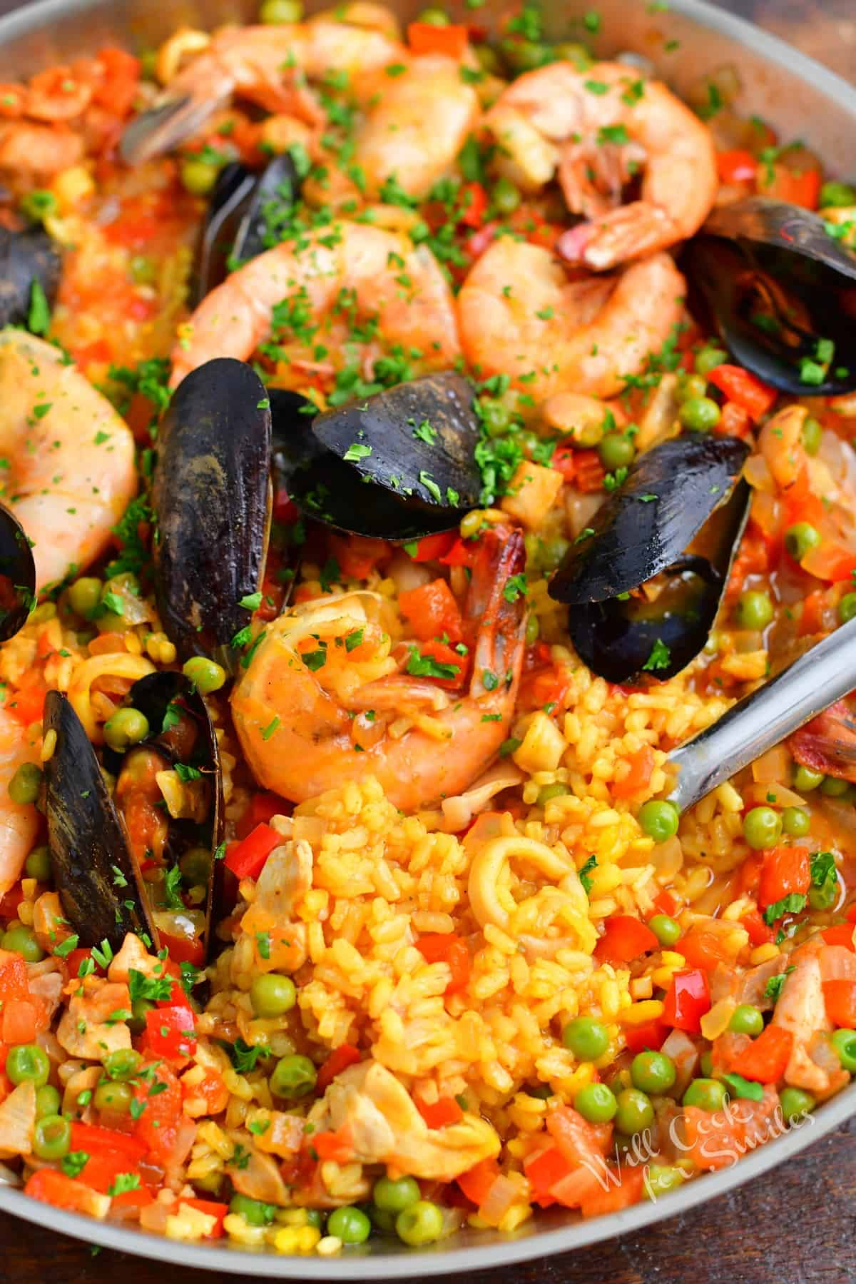 A serving spoon is in the process of removing a serving of paella from the pan.