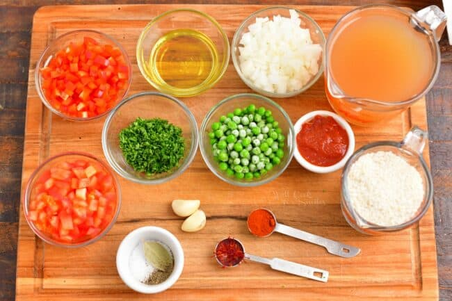 The ingredients for paella are placed on a wooden cutting board.