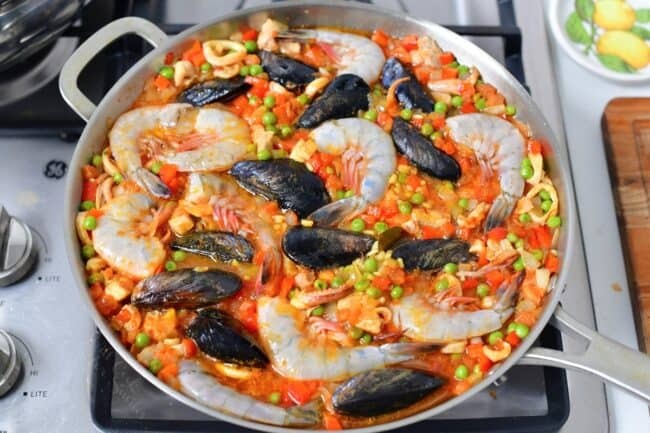 Shrimp and muscles are being cooked together with the paella.
