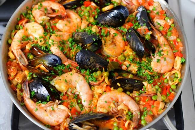 Paella is cooked and garnished, ready to be served.