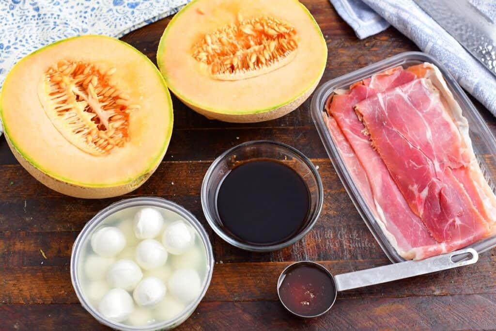 ingredients for prosciutto wrapped melon on a wood board