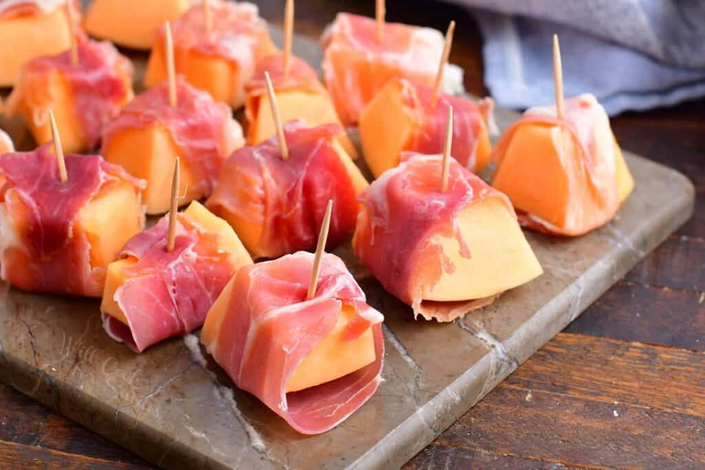 pieces of cantaloupe wrapped in prosciutto with a toothpick