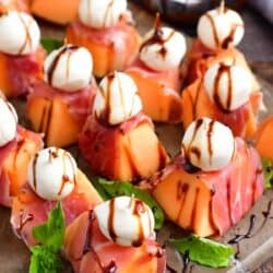 top view of melon wrapped in prosciutto with mozzarella ball and balsamic glaze