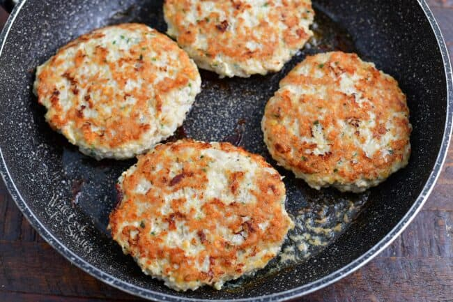 cooked chicken patties in a speckled cooking pan