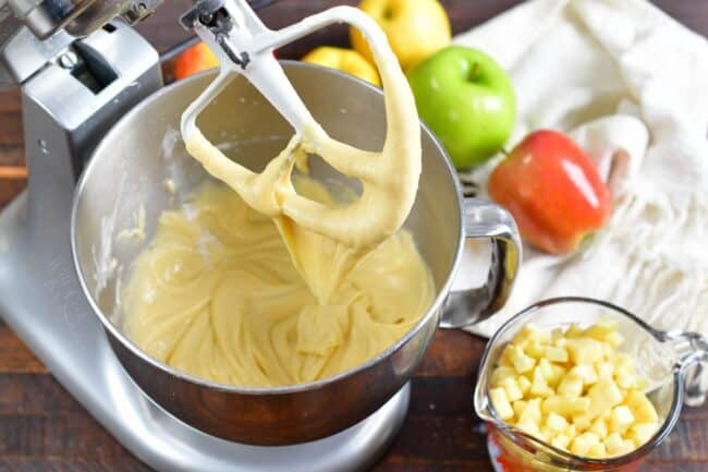 The batter is being mixed in a bowl, while a cup of diced apples sits on the side.