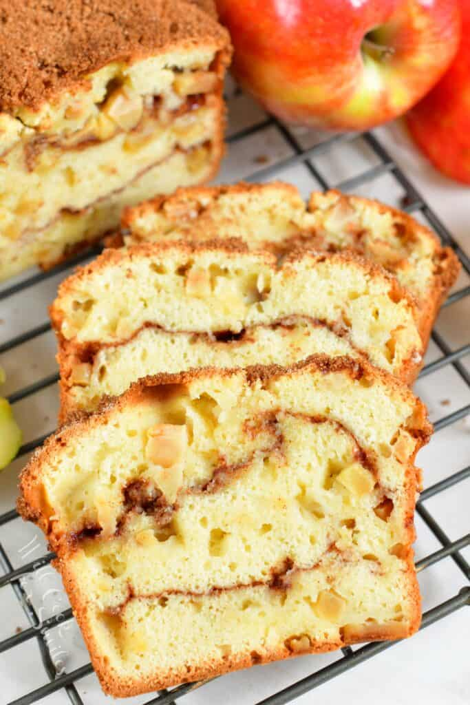 Four slices of apple bread are lined up on a wire cooling rack.