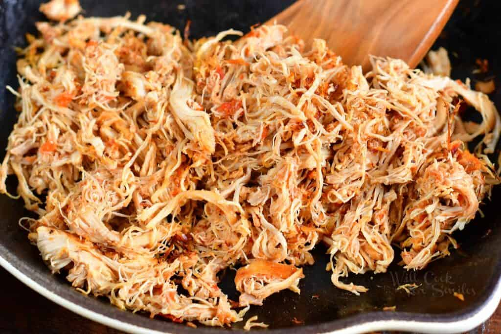searing shredded chicken in a pan