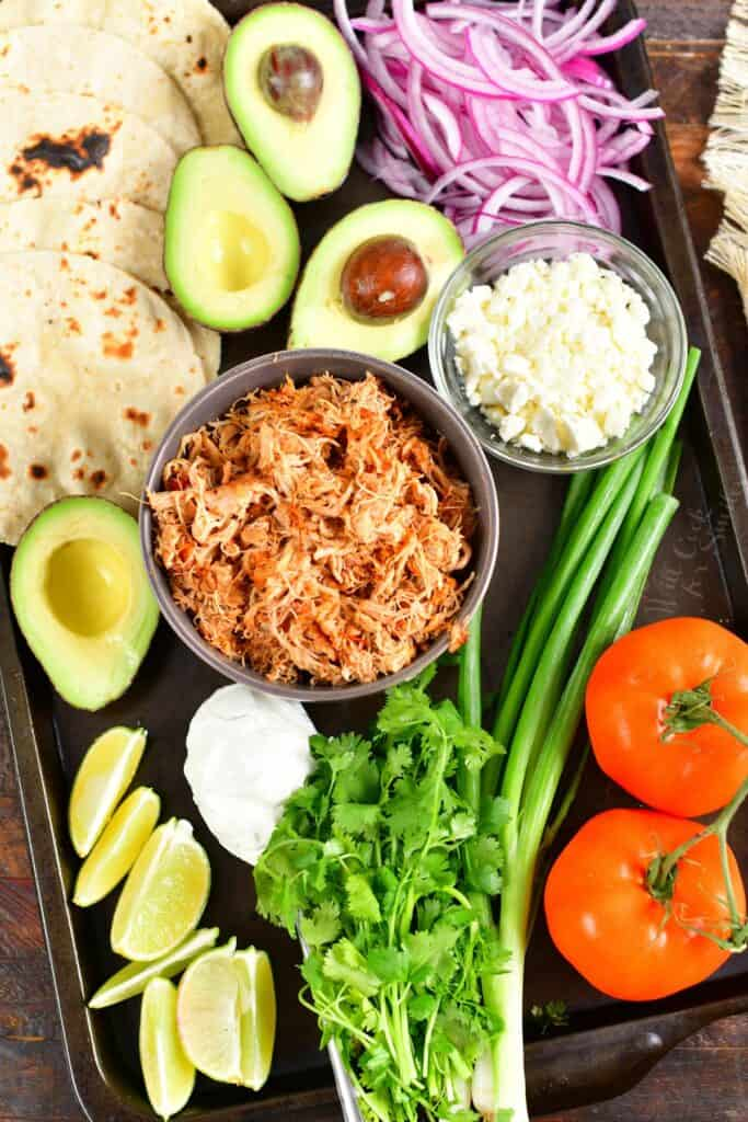 shredded chicken and toppings to make tacos laid out on a sheet pan