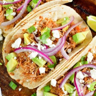 top view of the chicken tacos in a shell topped with onions and avocado