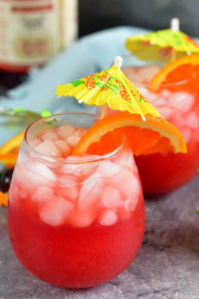 Two glasses are filled with a summery sweet cocktail on a gray countertop.