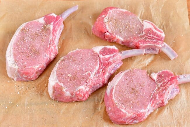 Raw pork chops are resting on a sheet of parchment paper.
