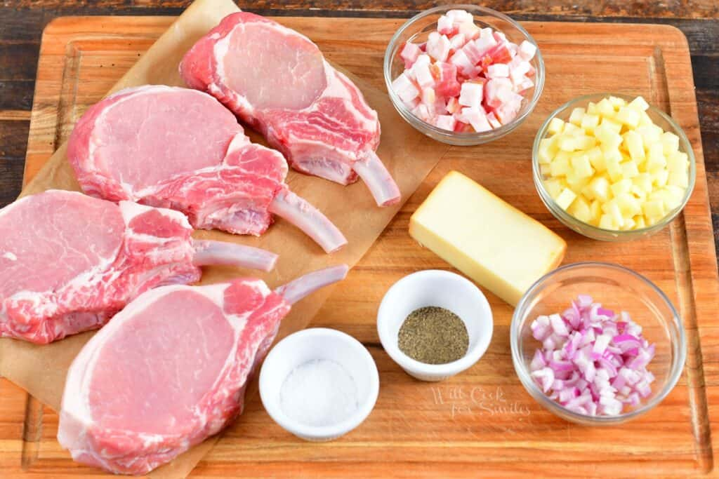 The ingredients for stuffed pork chops are placed on a wooden cutting board.