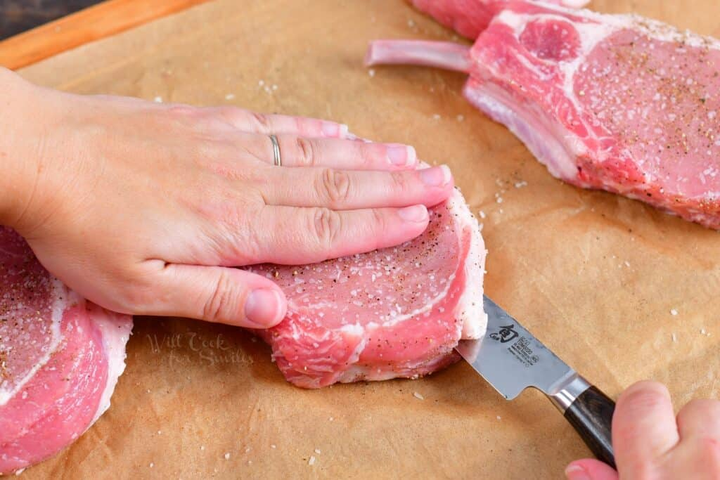 Raw pork chops are being sliced in half.