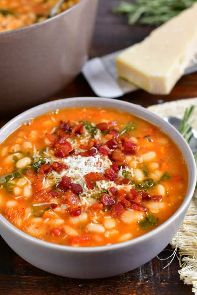 A bowl of soup is topped with parmesan and bacon bits.