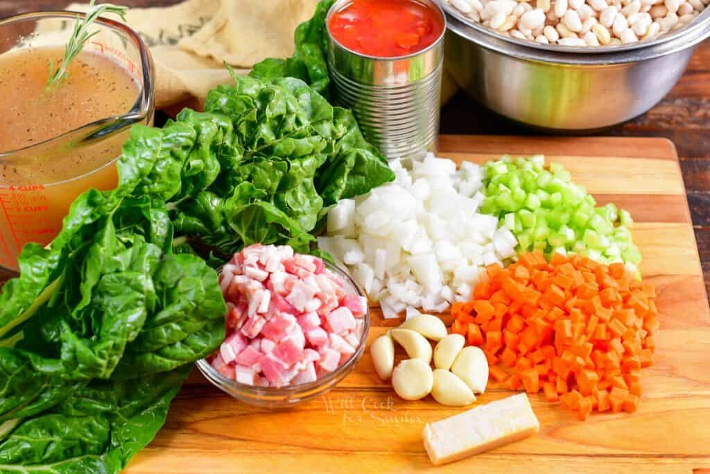 The ingredients for white bean soup are presented on a wooden cutting board.