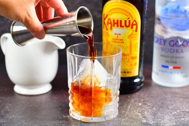 Adding Kahlua to the glass with vodka and ice