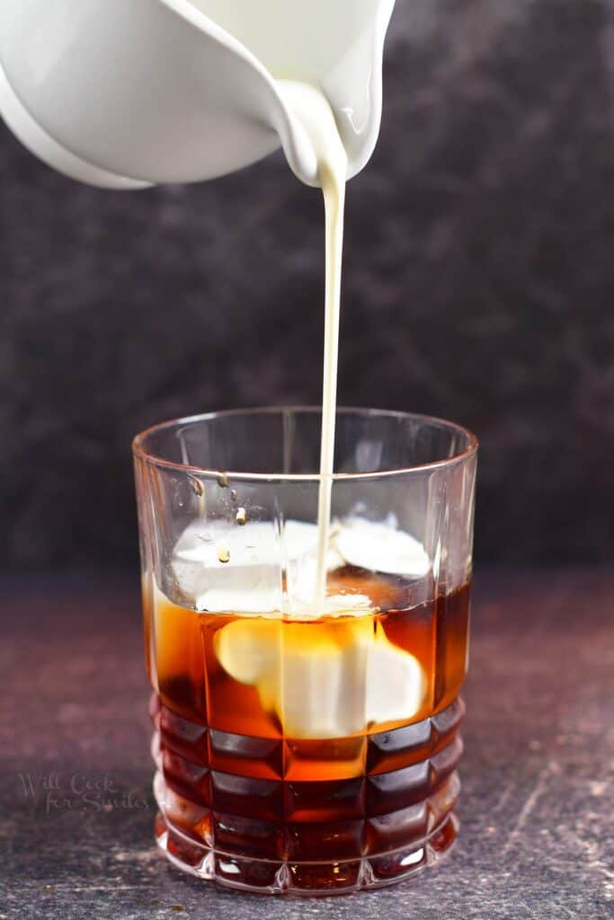pouring in heavy whipping cream into the cocktail glass with Kahlua and vodka