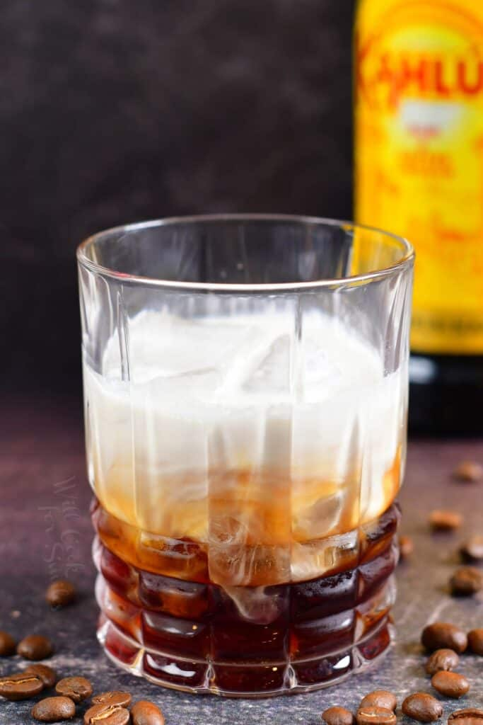 white Russian cocktail in a glass before mixing it to make creamy, layered look
