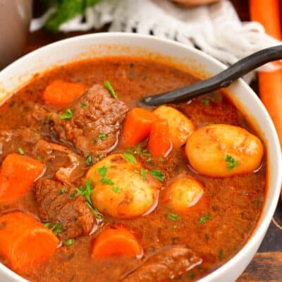 beef stew in a white bowl with a spoon in it