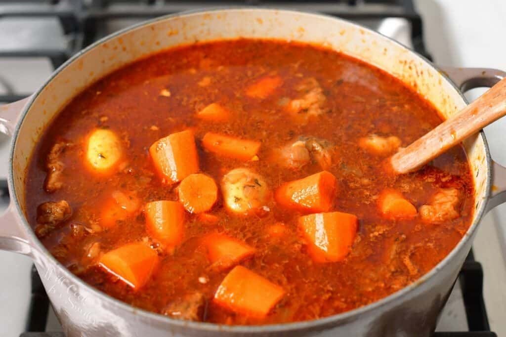 adding carrots and potatoes to the beef stew on a stove