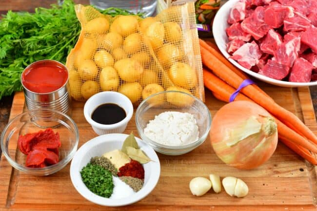 ingredients to make beef stew on a cutting board