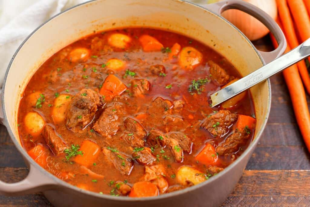 closeup of beef stew in a large pot with a ladle in it