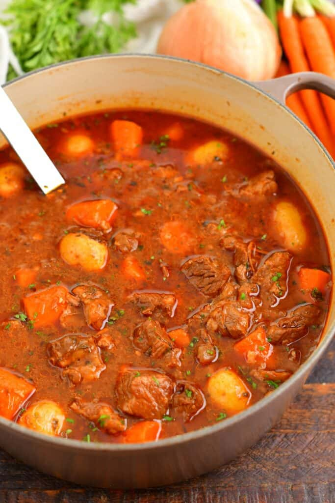 top view beef stew in a pot with vegetables around the pot
