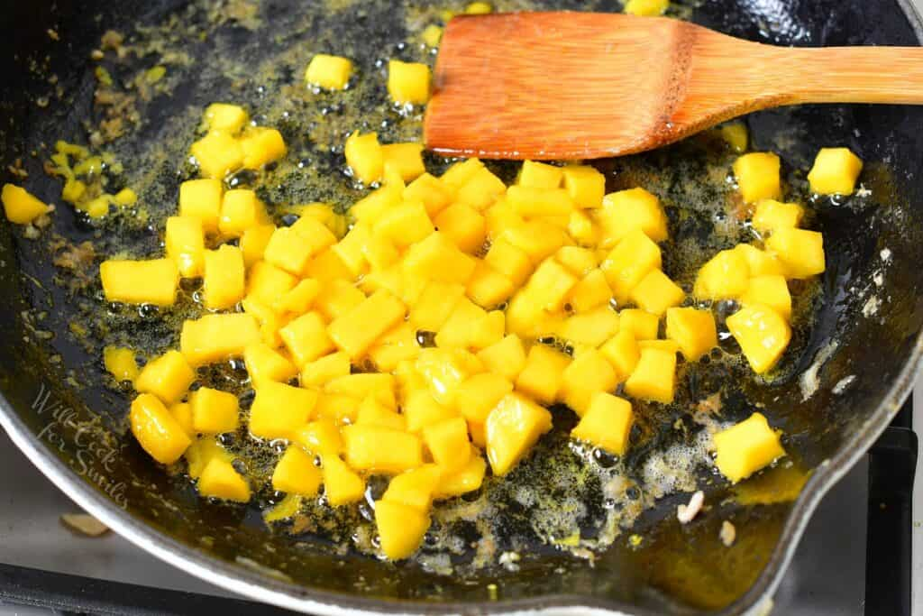 mango pieces cooking in a pan with a spatula visible
