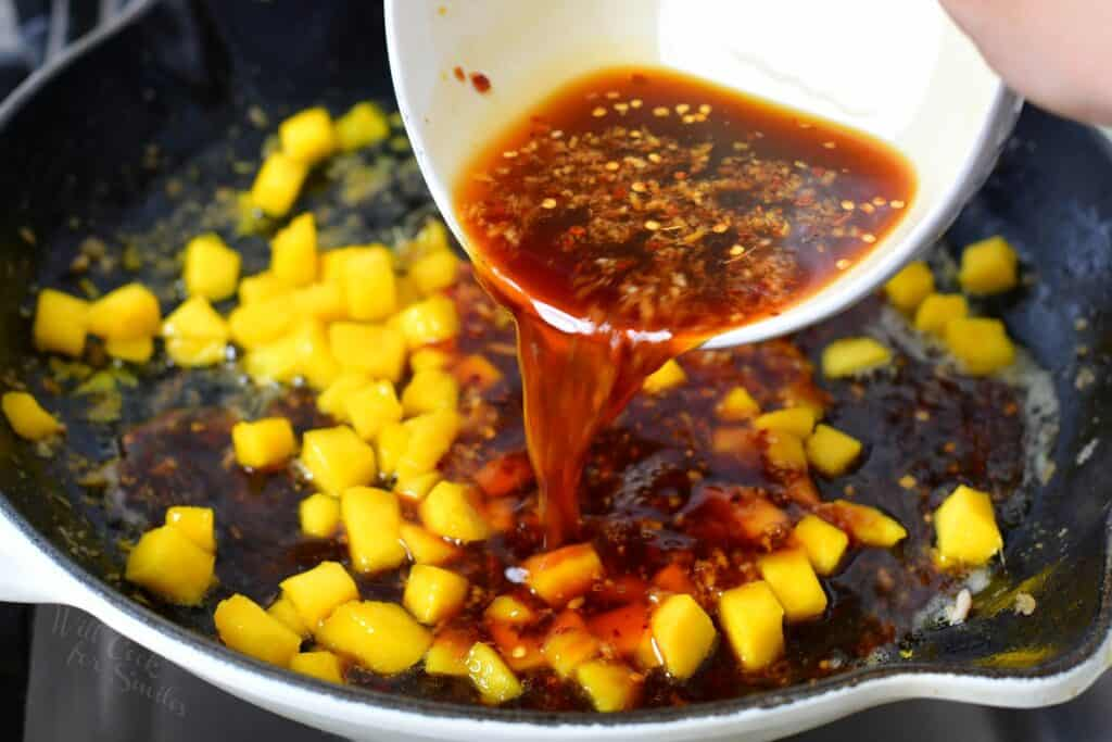 adding soy sauce mixture to the mango in a pan