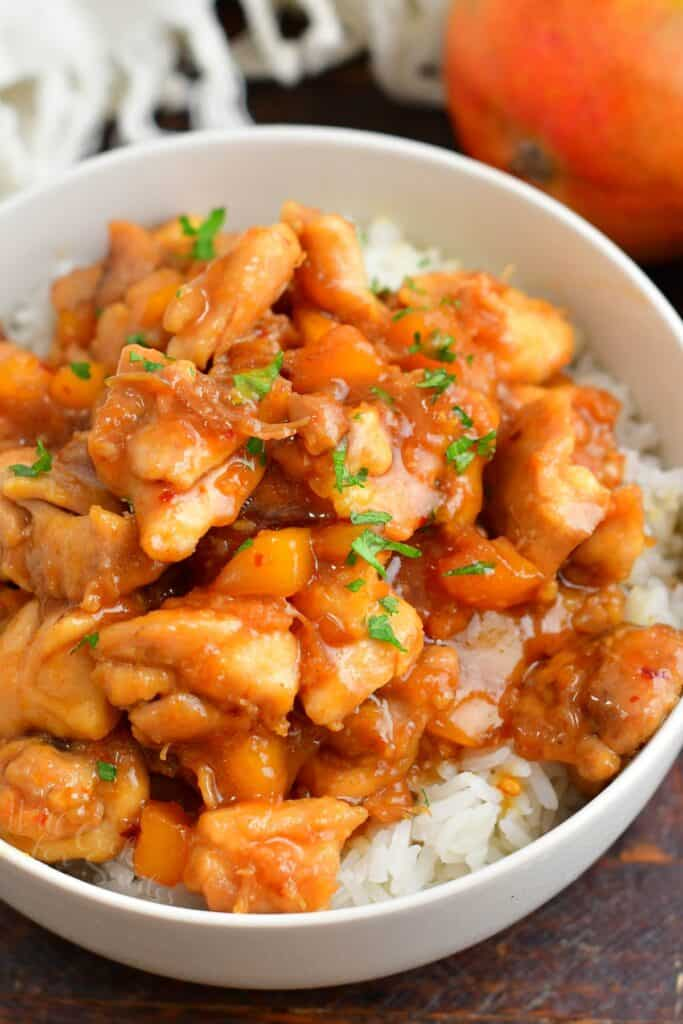 cooked mango chicken over rice in a white bowl