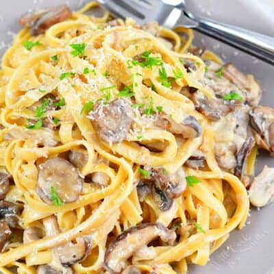 top view of pasta tossed in creamy mushroom sauce on grey plate