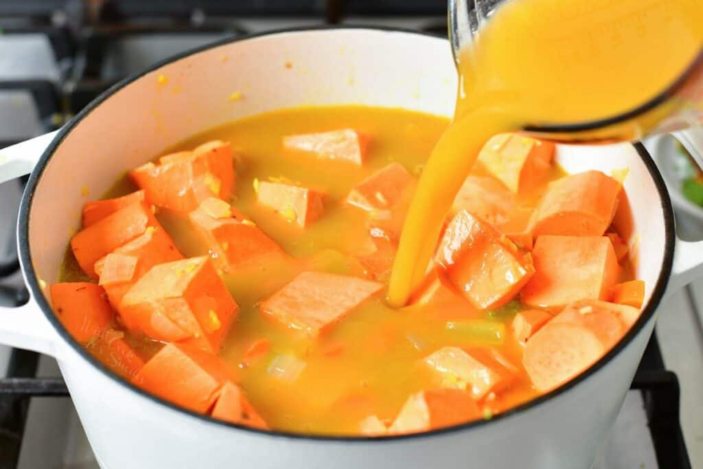 adding vegetable broth to the pot of sweet potatoes