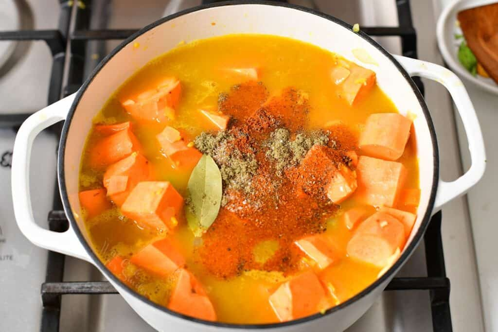 sweet potatoes covered in broth and topped with seasoning in a pot