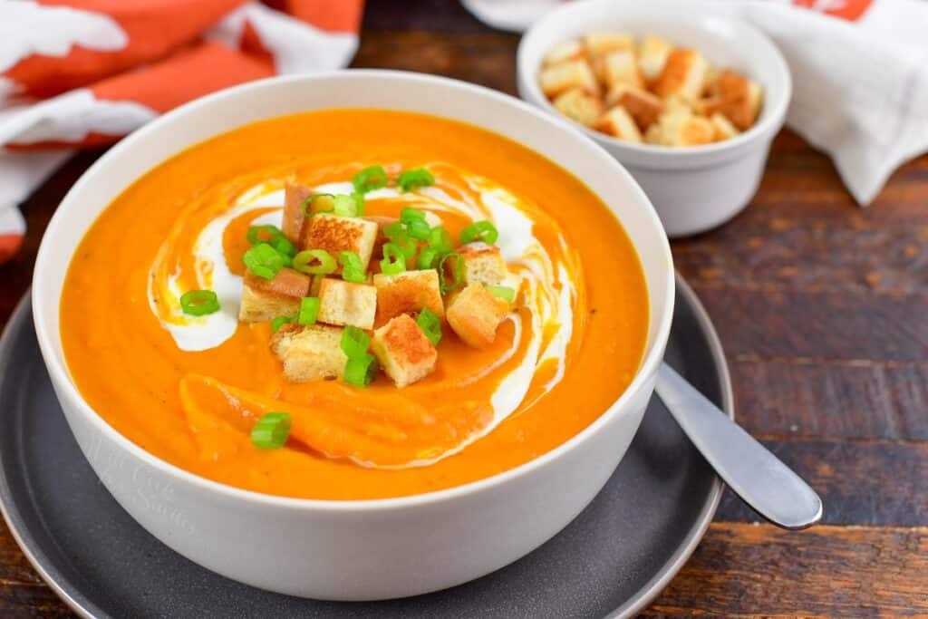 sweet potato soup in a bowl with croutons on top and next to the bowl