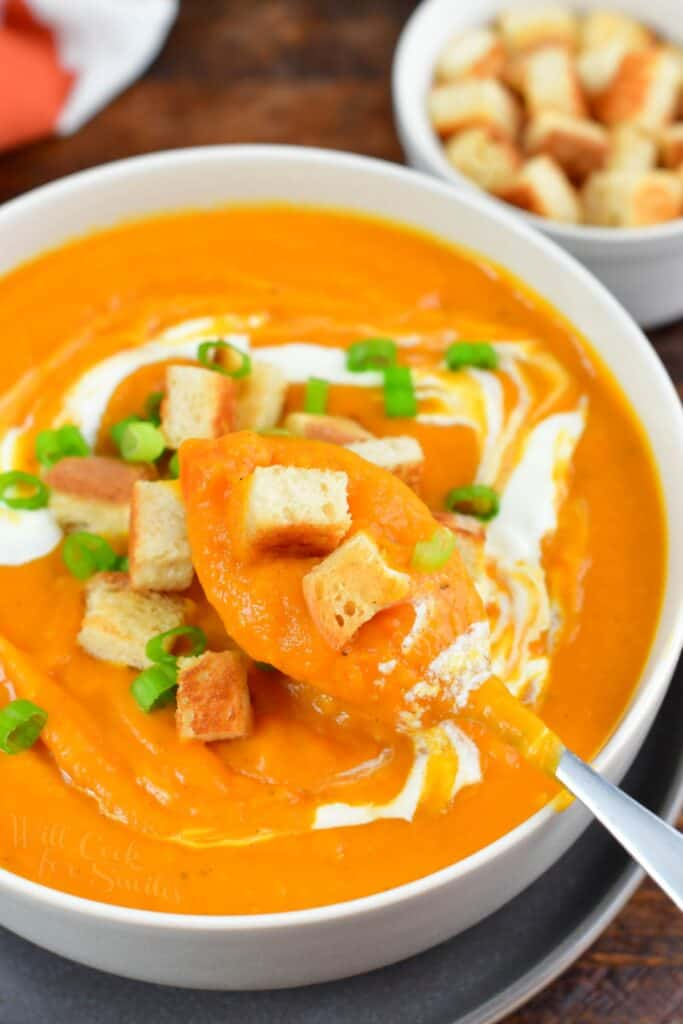 spooning out sweet potato soup out of a bowl