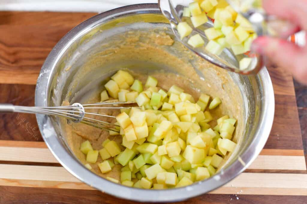 adding apples to the batter in a bowl